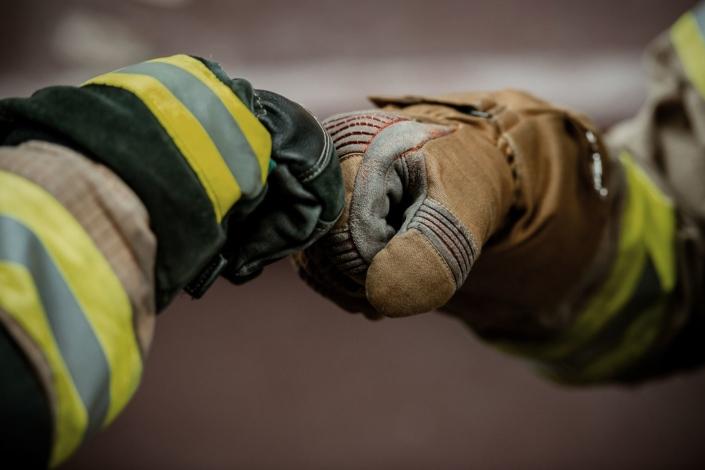 Feuerwehrleute begrüßen sich mit Faust