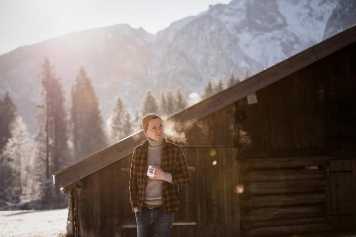 Mann mit Teetasse vor Hütte im Schnee