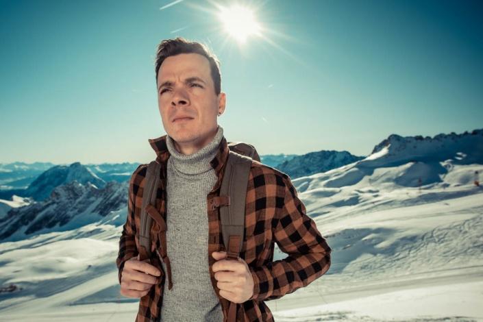 Mann mit Rucksack auf Gipfel im Schnee