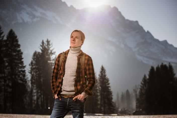 Mann in Outdookleidung vor schneebedeckten Bergen