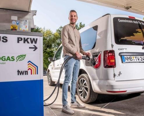 Mann tankt Erdgas an Tankstelle