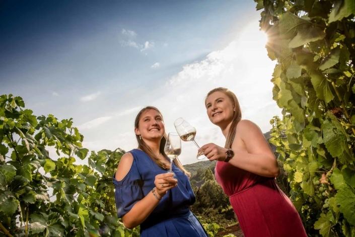 Frauen mit Weinglas im Weinberg