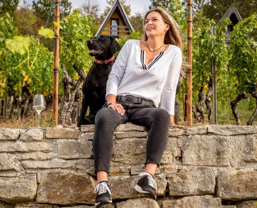 Frau mit Hund sitzt im Weinberg
