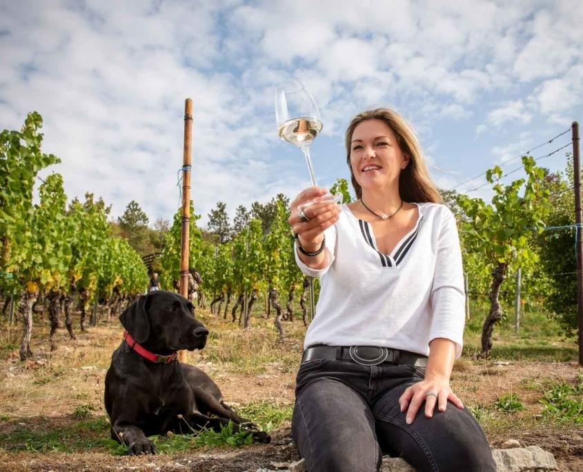 Frau mit Hund und Wein im Weinberg