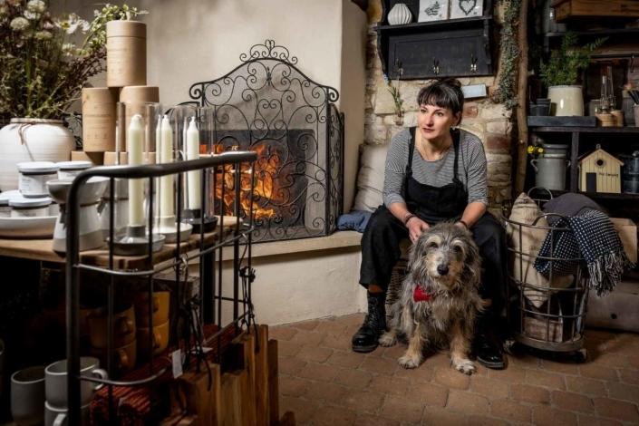 Frau mit Hund am Kamin im Laden